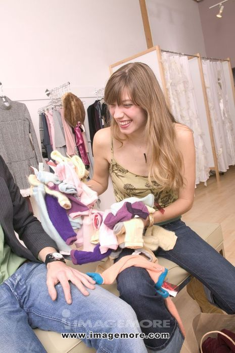 Caucasian Girl Holding A Pile Of Clothes And Laughing In A Fashionable Boutique
