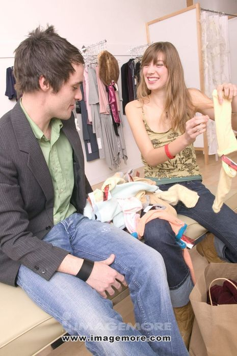 Stylish Caucasian Girl Sorting Through Clothes With A Fashionable Boy In A Trendy Boutique