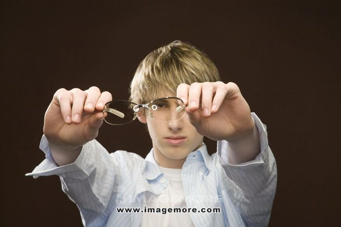 Teenage boy holding glasses