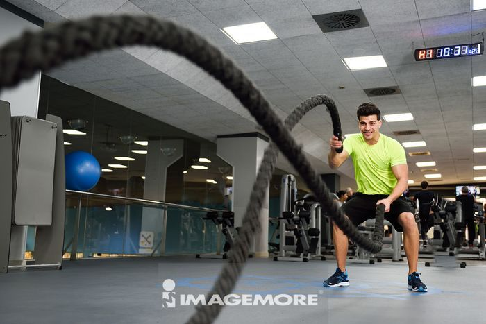 Man with battle ropes exercise in the fitness gym. Young male wearing sportswear.,