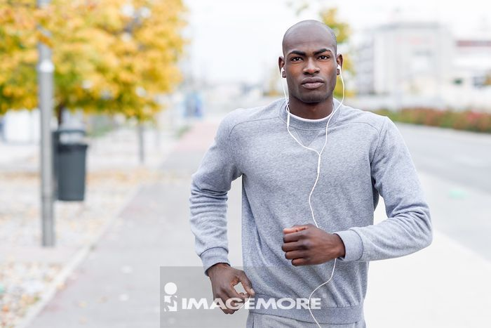 Attractive black man running in urban background. Male doing workout outdoors. Guy listening to music with white headphones,