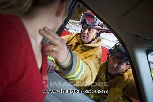Fireman taking woman's pulse while another fireman watches (selective focus)