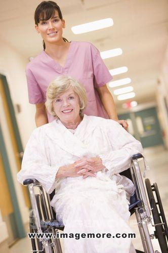 A Nurse Pushing A Senior Woman In A Wheelchair Down A Hospital Corridor