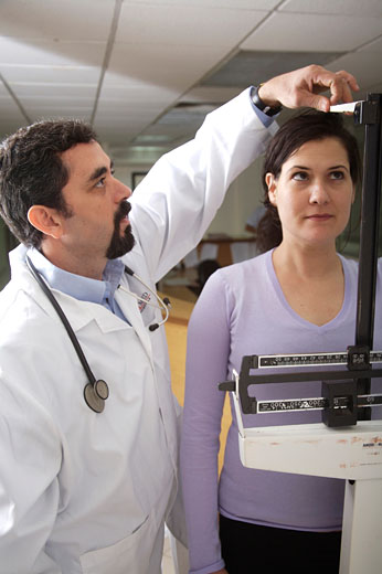Male doctor measuring the height and weight of a patient