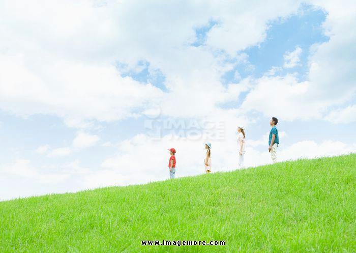 Family standing under blue sky