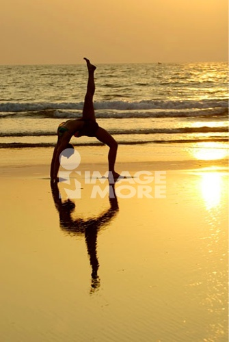 Silhouette of a woman practicing yoga on the beach, Morjim Beach, Goa, India