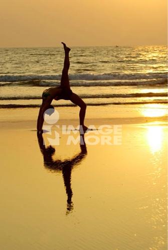 Silhouette of a woman practicing yoga on the beach, Morjim Beach, Goa, India