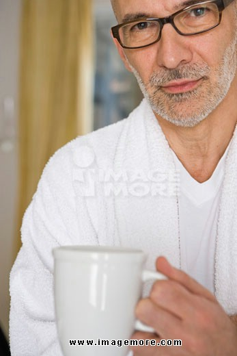 Portrait of a mature man holding a cup of coffee